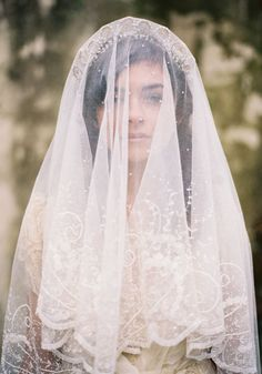 A bride wearing a veil how it originally came about which was by covering the whole face. This was to ensure the purity of a woman. Many times the veil would be past the shoulders and made with a trim of lace.