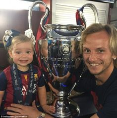 Ivan Rakitic and his daughter smile alongside the famous big-eared trophy after his opening goal in Berlin