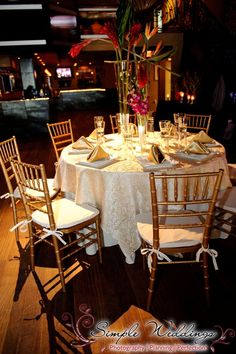 These gold chiavari chairs are the perfect finishing touch to this gold and ivory table setting with a bird of paradise centerpiece!