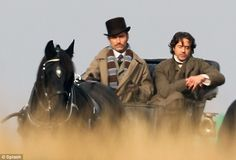 Take the reins: Jude Law drives a horse and carriage across Richmond Park in London as Robert Downey Jr sits beside him as the pair film the sequel to Sherlock Holmes