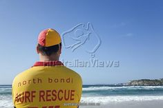 Australia, New South Wales, Sydney. A lifesaver watches the surf on Bondi Beach in eastern Sydney. Lifesavers are a common sight on Australian beaches, assisting swimmers in distress