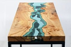 The amazing design here uses wood and glass to create a coffee table that mimics real life topography.