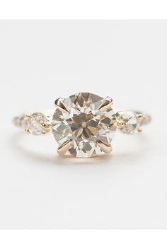 Brides.com: .  1.91 carat old European-cut white diamond accented by two old mine-cut white diamonds, price upon request, Mociun