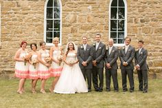 wedding party poses in front of stone church @myweddingdotcom
