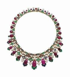 A RUBY, EMERALD, SAPPHIRE AND DIAMOND NECKLACE, BY MAUBOUSSIN. Of Indian inspiration, composed of ruby, sapphire, diamond or emerald trefoil and quatrefoil graduated motifs, suspending graduated pear-shaped cabochon rubies, to the circular-cut diamond detail, mounted in gold, 1967.