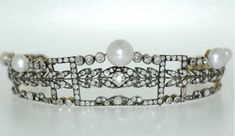 a delicate diamond and pearl tiara in three layers. Simple diamond base layer, diamond laurel leaf with central diamond on the middle layer, and the top layer of groups of three diamonds on each side of a large central button pearl