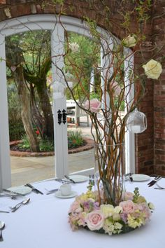Tall vases containing contorted willow decorated with sweet avalanche and avalanche roses, and glass balls containing tea lights.  Tall vase is surrounded by a ring of flowers of sweet avalanche and avalanche, memory lane, keira, juliet and vendella roses, stock and hydrangea