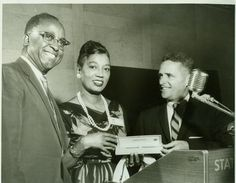North Carolina Mutual Life Insurance Company (NCMLIC): Carmen Enza Saunders, 1950s. Was the first person at NCMLIC to sell over a million dollars worth of insurance services. Here she is presented with an award (looks like a check) for her achievement.