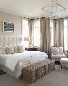 A peaceful bedroom created with neutral colors, flowing drapes & lots of pillows