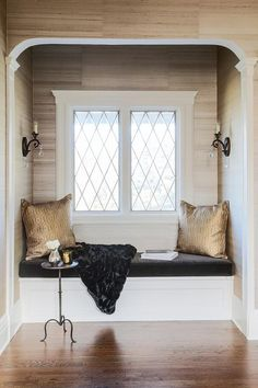 An arched reading alcove and window seat combo is clad in wallpaper lined with a black velvet seat cushions and gold metallic pillows illuminated by bronze French sconces.