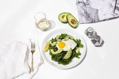 Massaged kale salad, topped with avocado and a sunny side up egg | @sakara
