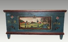 """Rare New England painted blue with cranberry red trim pine blanket chest dated 1834, original paint with truly wonderful folk art scene of man and women in village, original snipe hinges, dovetailed case with original tapered feet, 46 1/2"""" L x 23 1/2"""" D x 24"""" H."""