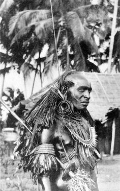 """A very fierce looking warrior from Papua, New Guinea, late 1800s. Under his arm is a """"skull smasher"""", the distinct war club of his tribe."""