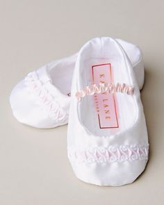 The Phoebe slipper offers just the right amount of pink to her all white gown.  https://www.onesmallchild.com/phoebe-christening-slippers.html