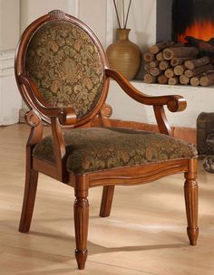 Create an old-world style with this beautifully crafted brocade arm chair. This lovely accent chair features an oval, cameo back design with dark brown and blue upholstery flecked with red and accented by rich solid wood arms and legs.