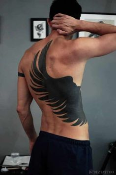 This minimal black silhouette is one of those wing tattoo ideas that definitely leaves an impact. Creating a sharp contrast against bare skin, the open wing represents absolute freedom as you let go of constraints and soar above all the things that have been holding you back. #tattoofriday #tattoos #tattooart #tattoodesign #tattooidea