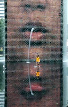 This is Crown Fountain in Millennium Park in Chicago. It is a 50-foot glass block tower that projects the faces of some chicagoans. Water gushes from their mouths into a shallow reflecting pool.