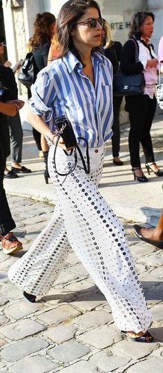 Leandra Medine in wide-leg Rosie Assoulin grommeted white pants and a blue striped button-down