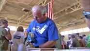 An Operation Gratitude volunteer helps assemble care packages for U.S. troops on Saturday, June 30, 2012.