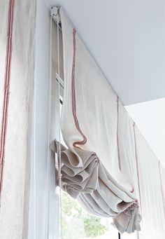 Feitos pela artesã Vera Marques, com a largura das janelas (90 cm), os tecidos são erguidos por meio de um sistema de monocontrole e, sem varetas, formam drapeados. Execução da Inova-se.