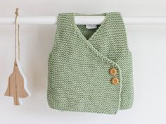 Hand knitted soft and warm wrap vest of 100% Superwash Merino wool. Great as an extra layer to keep your baby boy warm, this stylish vest is knitted
