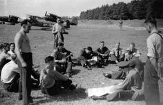 """Casually-attired flying personnel of III/6 Dywizjon receiving orders on 31 August 1939.The aircraft seen in front of the P.11 fighters parked in the background is an RWD-8 trainer, which had been requisitioned from a flying club prior to the outbreak of war. These machines would be used extensively for liaison duties until the end of the Polish campaign in October 1939. Photo and caption (a longer version) featured in Osprey Aircraft of the Aces 21 """"Polish Aces of ww2″"""