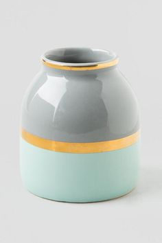 """The Grey &Mint Mini Vase withGold Stripewill be the perfect decorative accent to any room in your apartment or home!A bright & shiny gold stripestands out on the grey &mintbase. Pair with our additional home decor options to complete your room.<br /> <br /> - 3"""" x 4""""<br /> - Grey &mint painted base<br /> - Bold gold stripe<br /> - Material: ceramic<br /> - Imported<br />"""