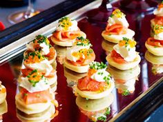 Blinis are a classic canape. Kick the party off right with bite-sized pancakes topped with delicious sour cream, smoked salmon and chives.