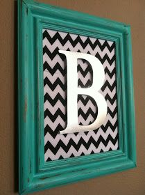 Fabric or scrapbook paper for a background with a painted initial in an open frame. Love this idea with hooks underneath for towels