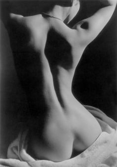 """ photo by Jeanloup Sieff (1992)"" The curves of a woman's back in shadow - black and white"