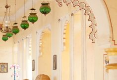 Loving the emerald hanging pendants offset by the white detailed arches.