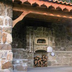 Four à bois traditionnel Le Panyol installé en extérieur sous une terrasse, habillage en pierre, plans de travail et rangements accessoires.