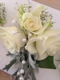 Soft ivory cottage roses and pearls for this pretty wedding corsage.