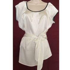 "NY&C SILKY TIE BLOUSE Silky and clean, white with black trim. Has detail at waist and tie front. Very clean. Worn once. 97% polyester, 3% spandex. Front panel about 16"" but still stretches; under arm to side hem is 16.5""; from where ties attaches to waist to longest end is 20""; arm holes about 6.5""; across collar about 12.5""; center point of collar to front hem 21.5""; underarm to underarm about 20"" New York & Company Tops Blouses"