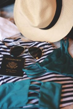 Winter holiday essentials: the swimsuit, French stripes, aviators, passport and a Panama hat.