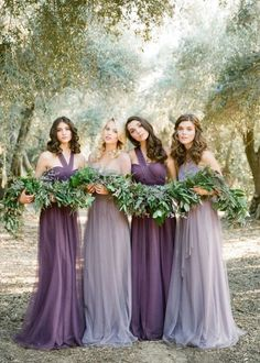 Lilac grey and plum long flowing bridesmaid dresses paired with elegant greenery for a formal spring wedding.