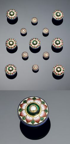 A set of Benares style gem-set enamelled gold Buttons consisting of seven larger and six smaller buttons, all decorated in pink green and white enamel with flowerheads set with diamonds, in a fitted case | Est. 3'000 - 5'000£ ~ (Oct '12)