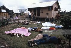 Investigators examine the compound of the People's Temple cult November 18, 1978 in Jonestown, Guyana after over 900 members of the cult, led by Reverend Jim Jones, died from drinking cyanide-laced Kool Aid; they were victims of the largest mass suicide in modern history.