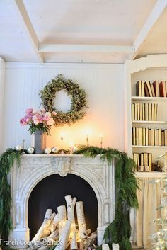 A Romantic Antique Fireplace Decorated for Christmas: Explore the French country details of this vintage marble fireplace with patina styled with simple Christmas decor items like evergreen garland and gold and silver ornaments. #frenchcountry #goldornaments