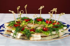 Канапе с пастой из соленого сала, запеченной телятины и свеженатертого хрена, намазанной между ломтиками белого хлеба, сверху - тонкие ломтики запеченной телятины, зелень, помидоры, оливки (украинская кухня).