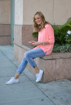 Distressed jeans, bright peach sweater, white sneakers
