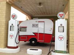 Perfect image of this Vintage camper alongside these old gas pumps