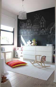 I'd suggest keeping the walls white. But take one wall, perhaps the one that borders the hallway, and cover it in chalk decals or paint it in chalk paint. Your family can draw pics on there for C. And the richness of the black will look really nice with the other elements.