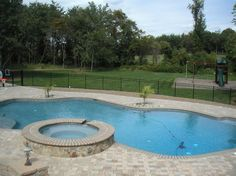 This beautiful, freeform, in-ground pool features a spa, and is surrounded by pavers which are very low-maintenance and bring natural tones and textures to any backyard. #ingroundpool #hottub #backyardlandscape http://www.anthonysylvan.com/pools-options.asp