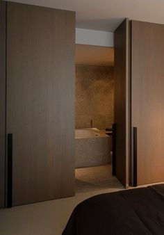 Wooden pivot door creating a nice and easy transition between bedroom and ensuite bathroom. (by Co. Studio):