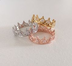 ♥ l i s t i n g d e t a i l s . .  This sweet and delicate ring features a princess crown pattern with cubic zirconia detail. The band is crafted from