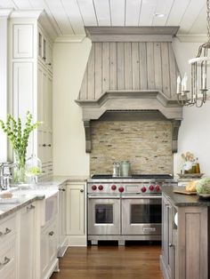 White Kitchen Cabinets with Grayed Wood Accents and Hood. Medium Dark Wood Floors
