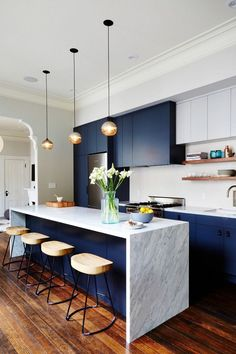 Modern kitchen with dark blue cabinents, a marble island, pendant lights, and wooden barstools