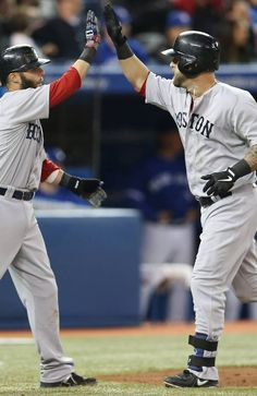 TORONTO, CANADA - APRIL 7: Mike Napoli #12 of the Boston Red Sox is congratulated by Dustin Pedroia #15 after hitting a 2-run home run in the eighth inning during MLB game action against the Toronto Blue Jays on April 7, 2013 at Rogers Centre in Toronto, Ontario, Canada. (Photo by Tom Szczerbowski/Getty Images)