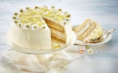 Dronningens fødselsdagslagkage Denne hvide kagedrøm er fantastisk elegant og består af de lækreste kagebunde bagt på mandelmel lagt sammen med hyldeblomstmousse og muscatskum. Pyntet med smukke spiselige blomster og flager af hvid chokolade er den selv en dronning værdig!